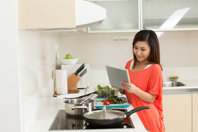 Asian woman cooking using tablet